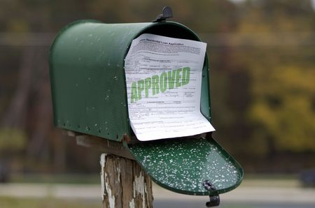Approved residential loan application sticking out of mailbox.  All information is fictional.