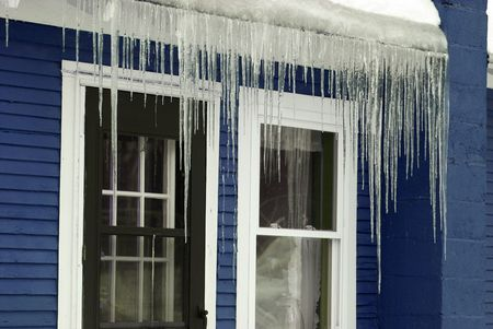 Icicles hanging off the roof of a blue house