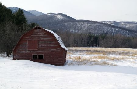 old red barn in the snow with mountains behind photo