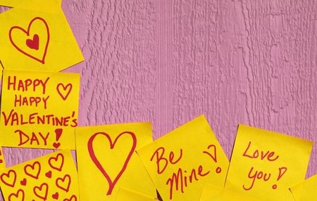 Yellow sticky notes on the border with valentine love messages writtern on them Stock Photo