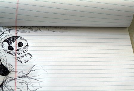 Pen doodle of skull on lines notebook paper