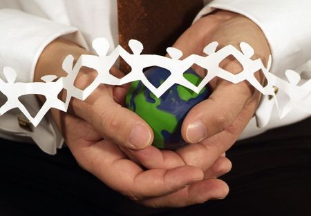 hands holding small green and blue globe with mini paper people across the globe photo
