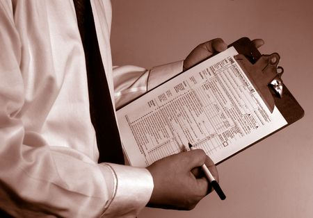 tax form: man in suit holding tax form Stock Photo