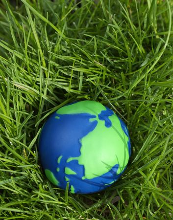 Green and Blue Globe with grass growing all around. Stock Photo