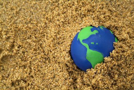 turismo ecologico: azul y verde planeta enterrados en la arena  Foto de archivo