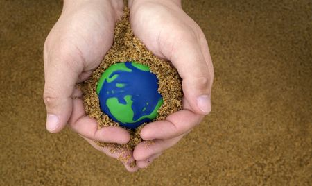 environmental issues: hands holding sand with small green and blue earth  Stock Photo