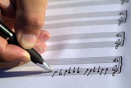 sheet music: Hand composing song on music sheet (selective focus on the pen)