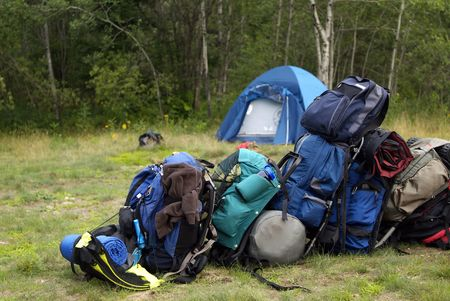 campsite: Blue Backpacking bags piled up in a line at the campsite Stock Photo