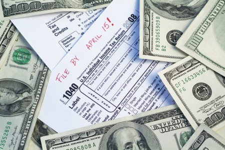 federal tax return: Blank 1040 Tax US Form surrounded by one hundred dollar american currency. Stock Photo