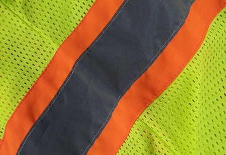 close up of a construction workers bright yellow and orange safety vest