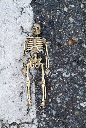 Skeleton with grungy background with dark stones and white line with skeleton in between.
