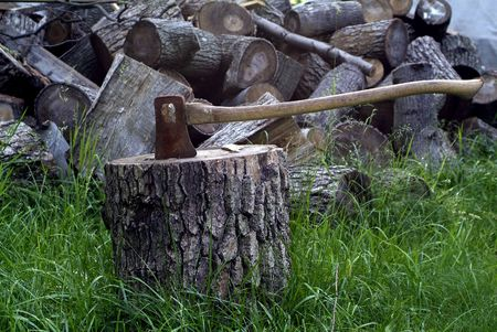 Axe splitting wood with pile of timber behind