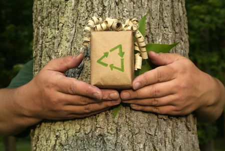 Unrecognizable Environmentalist person holding gift with recycling symbol in front of tree bark and leaf photo