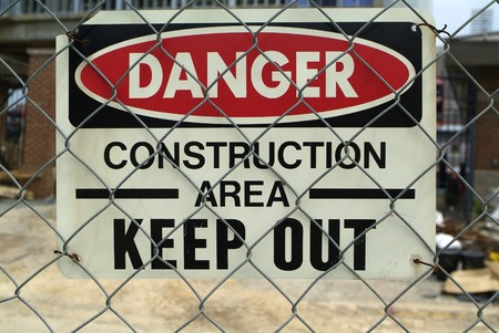 Construction Area Warning sign attached to a chainlink fence