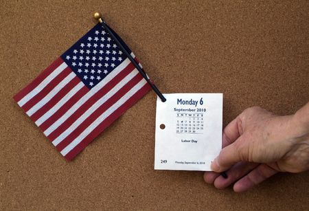 calandar: Hand of Person holding American Flag and Labor day calendar page for Monday September 6, 2010.