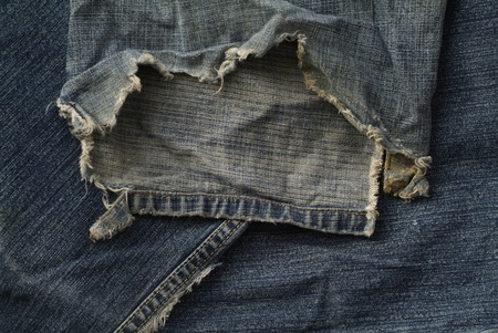 torn and frayed old blue jeans photo