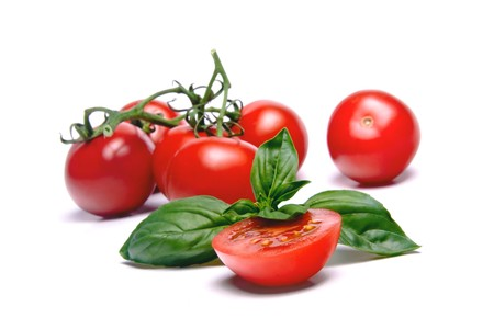 Halved Cherry Tomato & Basil leaf. More tomatoes on background.  Stock Photo - 4170768