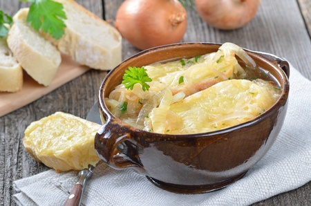 melted cheese: French onion soup with melted cheese on toasted baguette in a fictile bowl served on an old wooden table Stock Photo