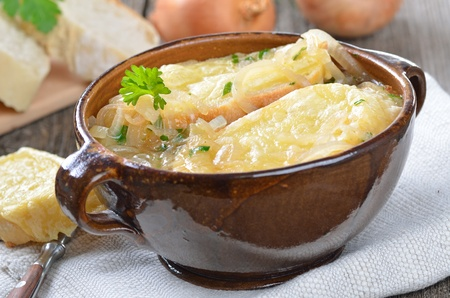 French onion soup with melted cheese on toasted baguette in a fictile bowl served on an old wooden table photo