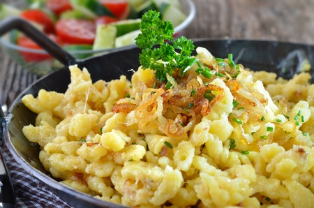 Southern German cheese noodles with fried onion rings photo