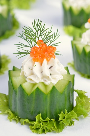 Fresh cream cheese with herbs and caviar on cucumber photo