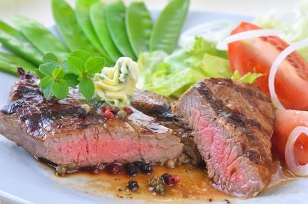 carnes y verduras: Filete de ternera a la parrilla con media tirabeques y ensalada de lado Foto de archivo