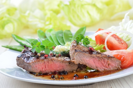 Medium grilled beef steak with sugar peas and side salad