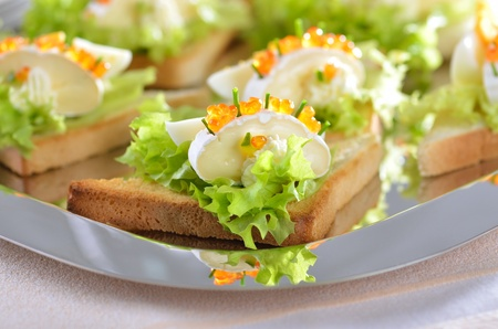 Delicious toast morsels with cheese (camembert), egg and trout caviar photo