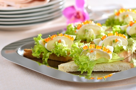 titbits: Delicious toast morsels with cheese (camembert), egg and trout caviar