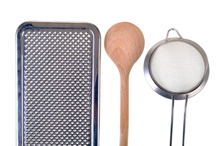 Whisk, wooden spoon, and a colander, isolated photo