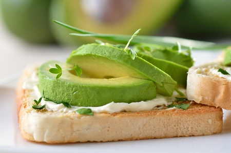 calorie rich food: Ripe avocado and cream cheese on toast Stock Photo