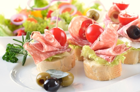 Baguette slices with delicious Italian salami and cherry tomatoes photo