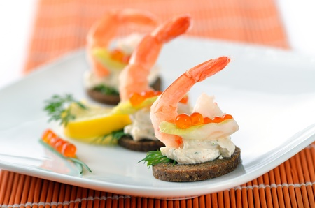 standing reception: Tidbits with prawns, spiced cream cheese and salmon caviar Stock Photo