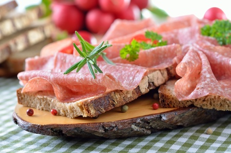 Farmhouse bread with delicious salami on a rustic wooden slice photo