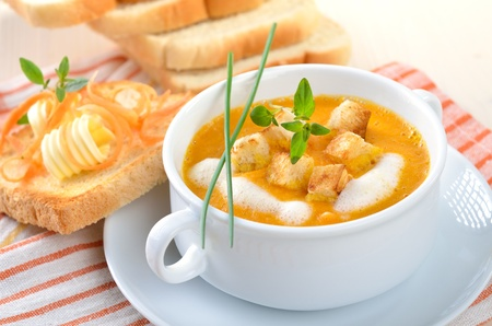 Carrot cream soup with croutons and toast photo