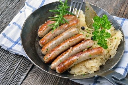 german food: Fried sausages on sauerkraut Stock Photo