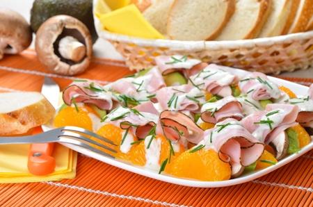 Colorful salad plate with avocado, champignons, mandarins and ham photo