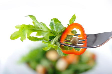 Fresh rucola salad on a fork