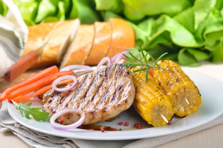 Grilled pork steaks with corncobs  photo