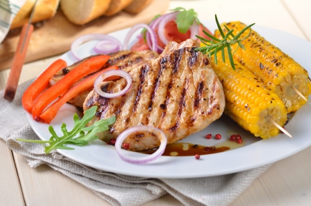 Grilled pork steaks with corncobs