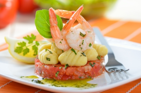 Italian gnocci and king prawns on tomato ragout with basil photo