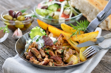 Greek gyros with tzatziki and fried potatoes, served in an iron pan
