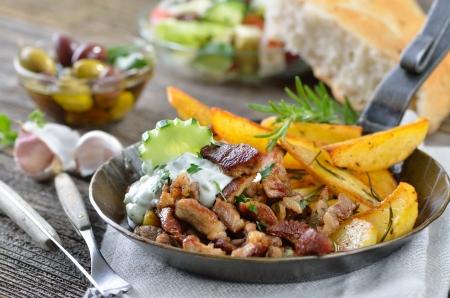 Griechischen Gyros mit Tzatziki und Bratkartoffeln, in einer eisernen Pfanne serviert