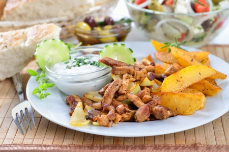 Greek gyros with tzatziki and fried potatoes photo