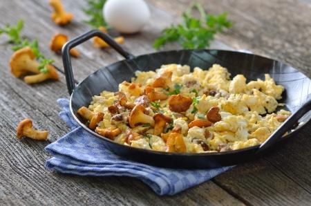 funghi: Uova strapazzate con finferli freschi in una padella che serve