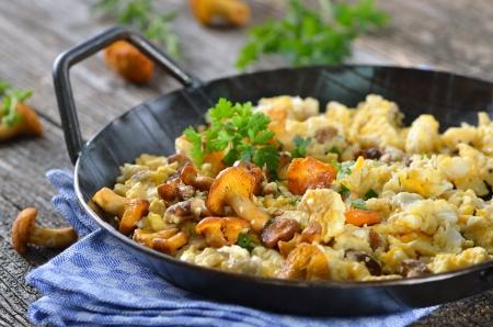 scrambled eggs: Huevos revueltos con rebozuelos frescos en una bandeja de servir