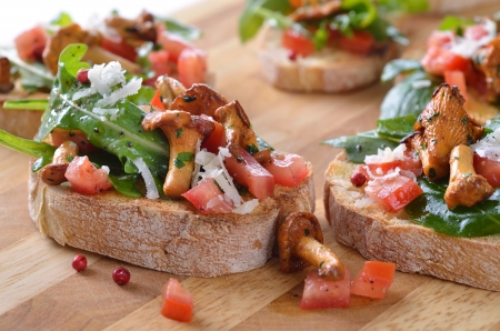 chanterelle: canapes with rucola-tomato-salad and fried chanterelles
