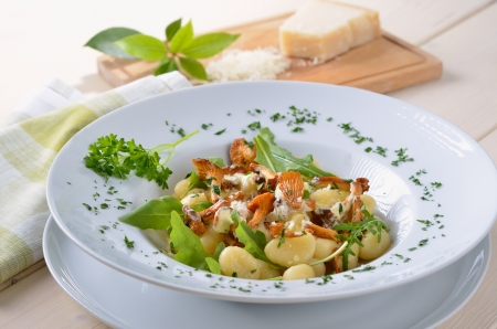 fine cuisine: Gnocchi with fried chanterelles, sauce, rucola and parmesan Stock Photo
