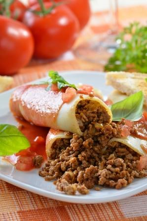 Italiaanse cannelloni gevuld met gehakt en geserveerd met tomatensaus Stockfoto