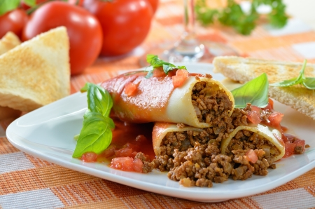 Italian cannelloni stuffed with minced meat and served with tomato sauce Archivio Fotografico